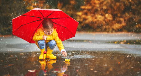 Photo pour happy child girl with umbrella and paper boat in a puddle in   autumn on nature - image libre de droit