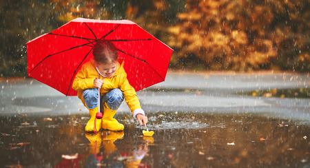 Foto de happy child girl with umbrella and paper boat in a puddle in   autumn on nature - Imagen libre de derechos