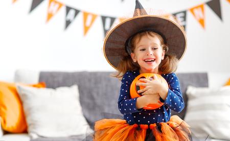 Foto de happy laughing child girl in witch costume to halloween  - Imagen libre de derechos
