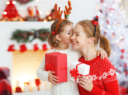 Foto de happy family mother and daughter giving christmas gift and embracing - Imagen libre de derechos