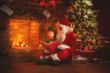 Photo for santa claus reads a book to a little elf by fireplace and Christmas tree  - Royalty Free Image