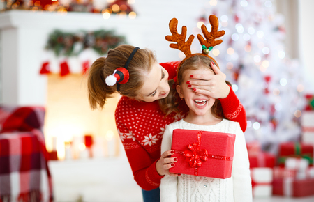Photo pour happy family mother and daughter giving christmas gift and embracing - image libre de droit