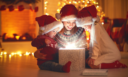 Photo pour Merry Christmas! family mother and children with magic gift at home near  Christmas tree and fireplace - image libre de droit