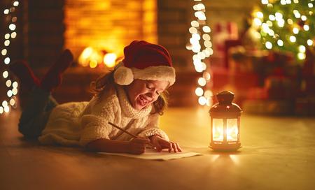 Foto de child girl writing letter santa home near the Christmas tree  - Imagen libre de derechos
