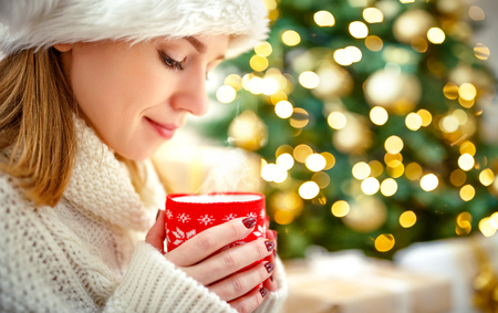 Photo pour happy woman with a mug of tea near a Christmas tree  - image libre de droit