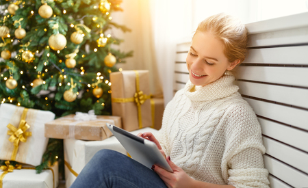 Photo pour happy woman with with tablet pc at morning near a Christmas tree  - image libre de droit