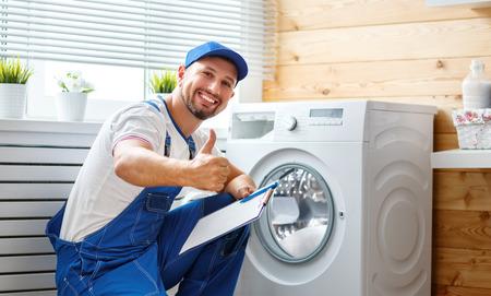 Foto de working man plumber repairs a washing machine in   laundry  - Imagen libre de derechos