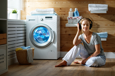 Foto de a Happy housewife woman listens to music on headphones in laundry room with washing machine    - Imagen libre de derechos