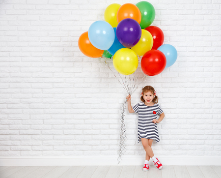 Foto de Happy funny child girl with a colorful balloons near an empty white brick wall  - Imagen libre de derechos