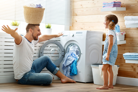 Foto de Happy family man father  householder and child daughter in laundry with washing machine   - Imagen libre de derechos