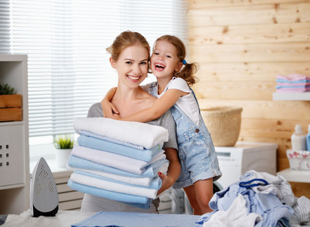Foto de Happy family mother housewife and child daughter  ironing clothes iron in laundry at home  - Imagen libre de derechos