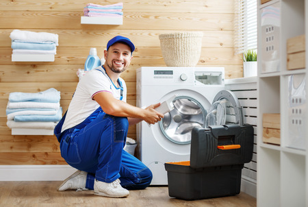 Photo pour working man plumber repairs a washing machine in   laundry  - image libre de droit
