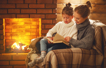 Photo for happy family mother and child daughter read a book on winter autumn evening near fireplace  - Royalty Free Image