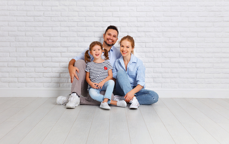 Photo pour happy family mother father and child daughter near an empty brick wall  - image libre de droit