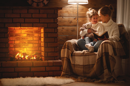 Foto de happy family mother and child daughter read a book on winter autumn evening near fireplace  - Imagen libre de derechos