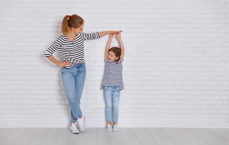 Photo pour concept of the family. mother measures growth of child to a daughter near an empty wall  - image libre de droit