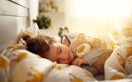 Photo pour  child  girl sleeps in her bed with a toy teddy bear  in morning  - image libre de droit