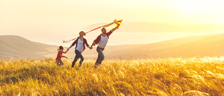 Photo pour Happy family father,  mother and child daughter launch a kite on nature at sunset  - image libre de droit