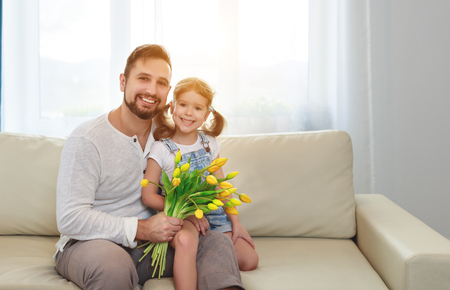 Photo pour father and child daughter with a bouquet of flowers at home  - image libre de droit