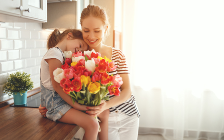 Foto de happy mother's day! child daughter congratulates mother and gives a bouquet of flowers to tulips  - Imagen libre de derechos