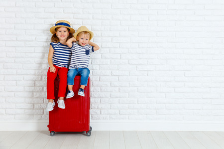 Photo pour happy laughing children boy and girl with suitcase going on a trip  - image libre de droit