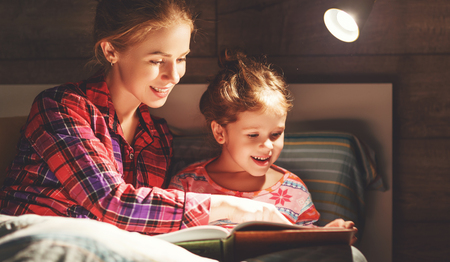 Photo pour mother and child daughter reading book in bed before going to sleep   - image libre de droit