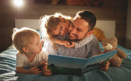Foto de evening family reading. father reads children a book before going to bed   - Imagen libre de derechos