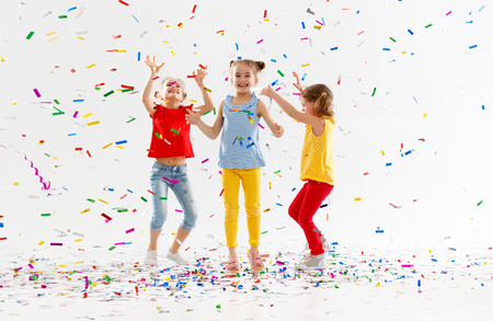 Photo pour happy children on holidays have fun and  jumping in multicolored confetti on white background  - image libre de droit