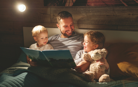 Photo for evening family reading. father reads children a book before going to bed   - Royalty Free Image