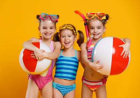 Foto de funny funny happy children  jumping in swimsuit and swimming glasses jumping on colored background  - Imagen libre de derechos
