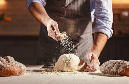 Foto de hands of the baker's male knead dough - Imagen libre de derechos