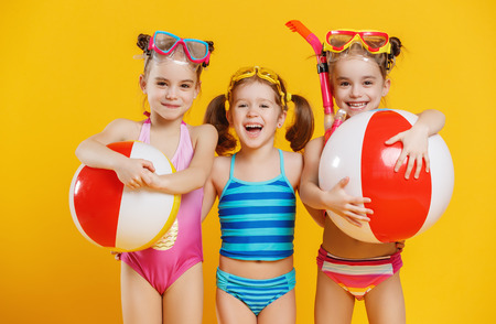 Photo for funny funny happy children  jumping in swimsuit and swimming glasses jumping on colored background  - Royalty Free Image
