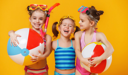 Foto de funny funny happy children in bathing suits and swimming glasses jumping on colored background  - Imagen libre de derechos