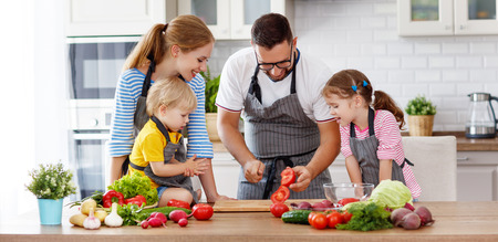 Foto de happy family with children preparing vegetable salad at home  - Imagen libre de derechos