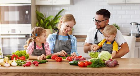Foto de Happy family with child  preparing vegetable salad at home - Imagen libre de derechos
