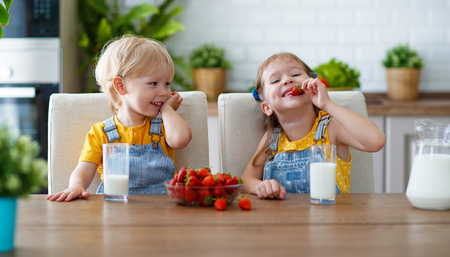 Foto de Happy children girl and boy brother and sister eating strawberries with milk - Imagen libre de derechos