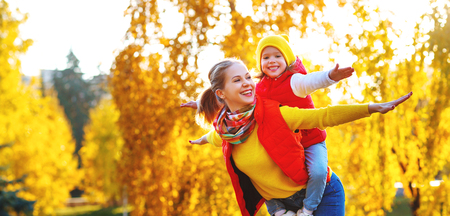 Foto de happy family mother and child daughter playing and laughing on   autumn walk - Imagen libre de derechos