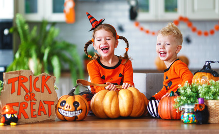 Photo for happy children in costumes of pumpkins are preparing the home for holiday Halloween - Royalty Free Image