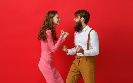 Foto de happy couple won emotionally celebrating win on   colored red background - Imagen libre de derechos