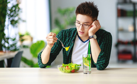 Foto per healthy eating. happy young man eating salad in the morning in kitchen - Immagine Royalty Free