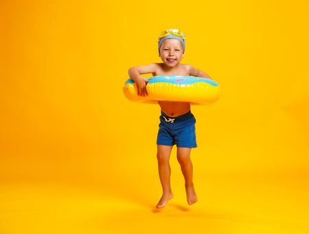 Photo for happy child boy in swimsuit with swimming ring donut on a colored yellow background - Royalty Free Image