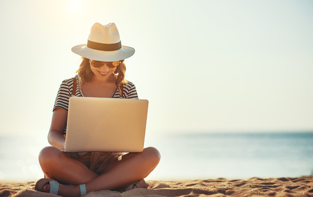 Photo pour young woman working with a laptop on nature in summer beach - image libre de droit