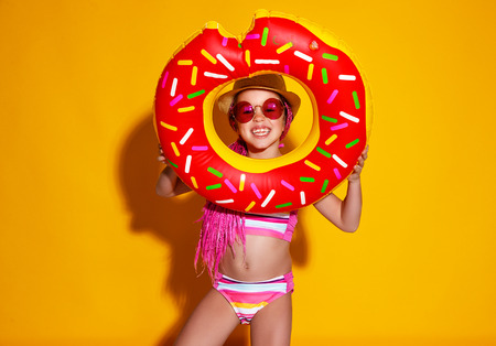 Photo for Happy child girl in swimsuit with swimming ring donut on a colored yellow background - Royalty Free Image
