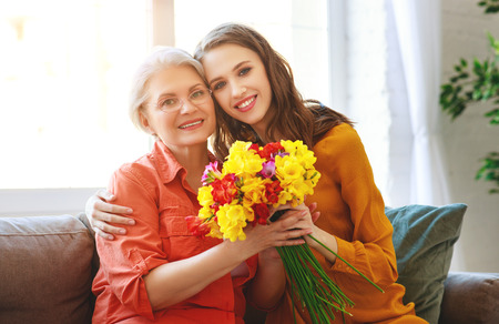 Photo pour Happy mother's day! Adult daughter gives flowers and congratulates an elderly mother on the holiday - image libre de droit
