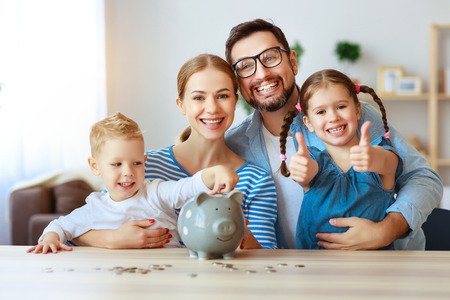 Photo pour Financial planning happy family mother father and children with piggy Bank at home - image libre de droit