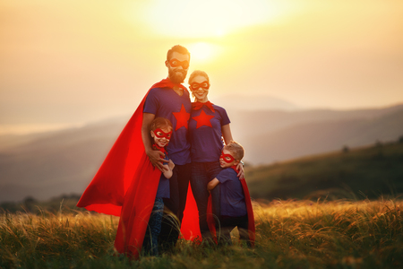 Foto de concept of super family, family of superheroes at sunset in nature - Imagen libre de derechos