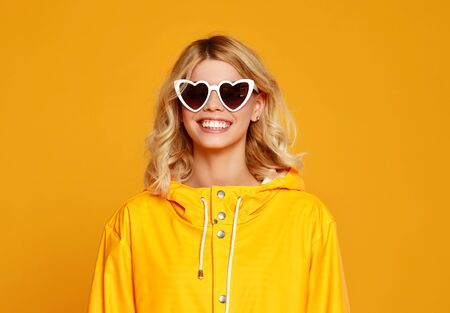 Photo pour the happy emotional girl with sunglasses on autumn colored yellow background - image libre de droit