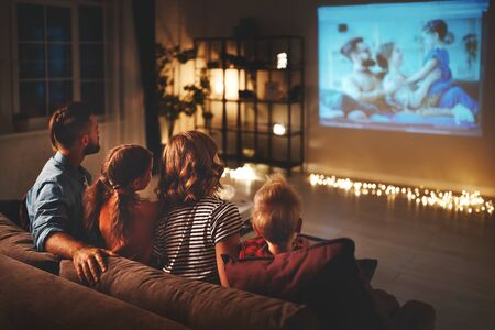 Photo for family mother father and children watching projector, TV, movies with popcorn in the evening   at home - Royalty Free Image