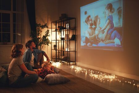 Photo pour family mother father and children watching projector, TV, movies with popcorn in the evening   at home - image libre de droit