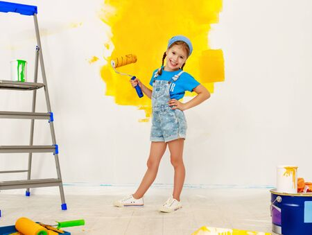 Photo for Repair in the apartment. Happy child girl paints the wall with yellow paint - Royalty Free Image